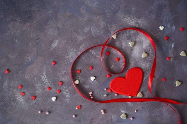 赤いハートとバレンタインのコンクリート背景。グリーティングカードの背景