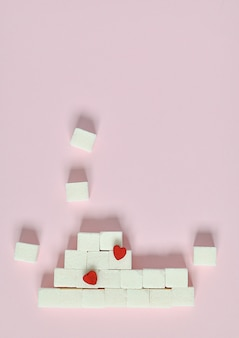 ピンクの背景に白の砂糖の立方体。糖尿病とカロリー摂取の概念は何ですか