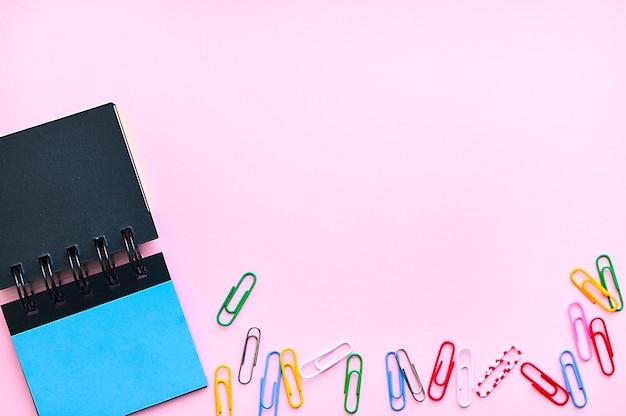 コピースペースと事務机の上のペーパークリップと付箋。ビジネス、教育の概念ノート。フレームピンク色。
