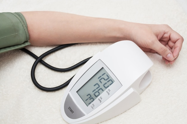 Женщина заботится о здоровье и измеряет свое кровяное давление