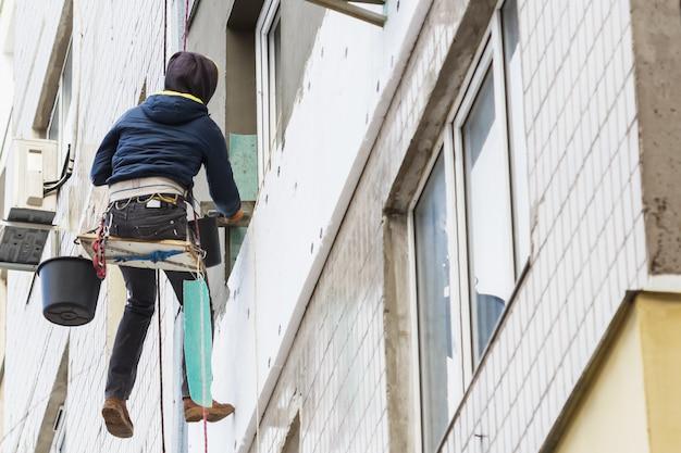 Утепление наружной стеновой панели. рабочий человек изолирует стены многоэтажного здания