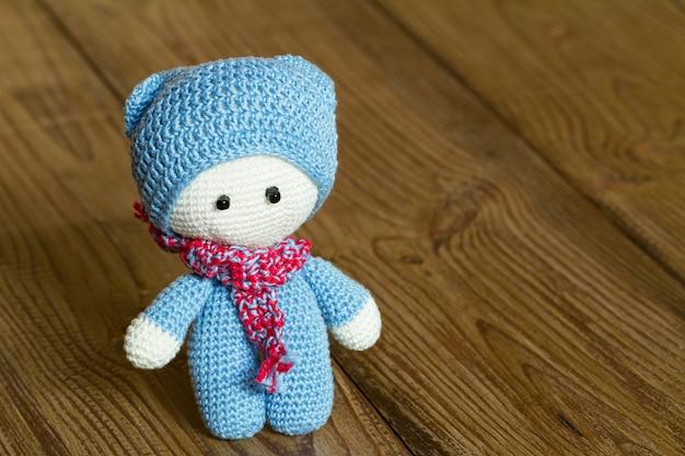 かぎ針編みの柔らかいおもちゃ、木製の背景