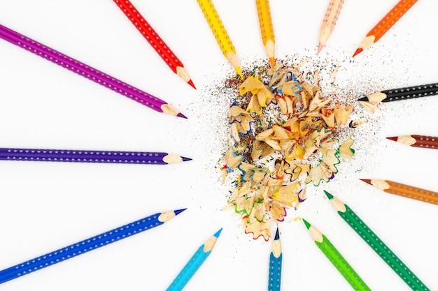 Разноцветные карандаши на светлом фоне рядом со строгальной и карандашной стружкой.