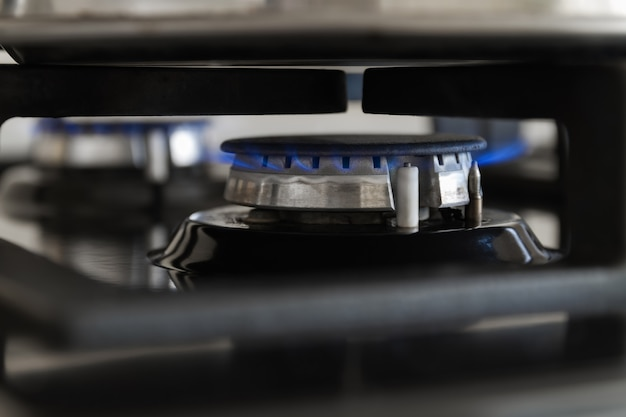 Сжигание газа с кухонной газовой плитой. голубое газовое пламя на варочной панели. макрофотография, выборочный фокус