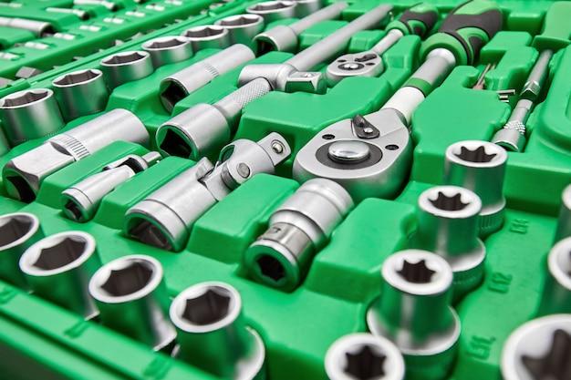 異なるノズルとビットが設定された大きな緑色のツールボックス。クローズアップ、セレクティブフォーカス