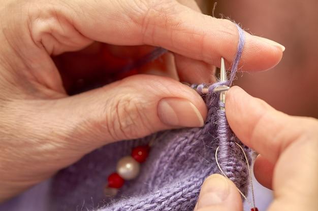 女性は青い暖かいセーターを編んでいます。年配の女性の趣味は編み物です。編み物ループのクローズアップビュー。セレクティブフォーカス