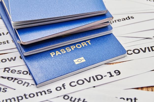新聞の見出しの切り抜きの背景にあるパスポート。コロナウイルスと旅行の概念。ウイルスによる国間の国境の閉鎖。閉じる
