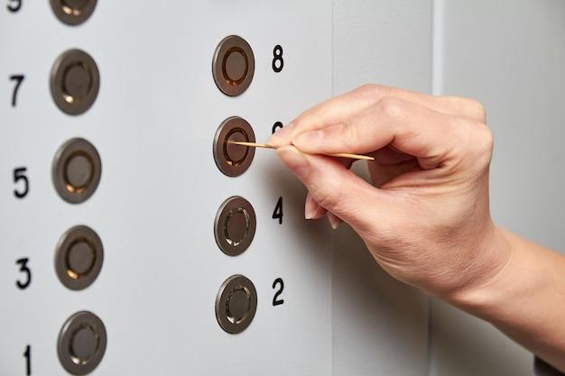 Женщина нажимает кнопку лифта с зубочисткой