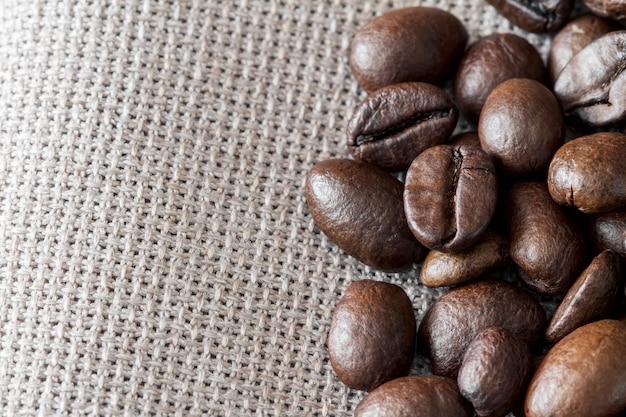 コピースペースとリネンの生地にコーヒー豆のクローズアップ
