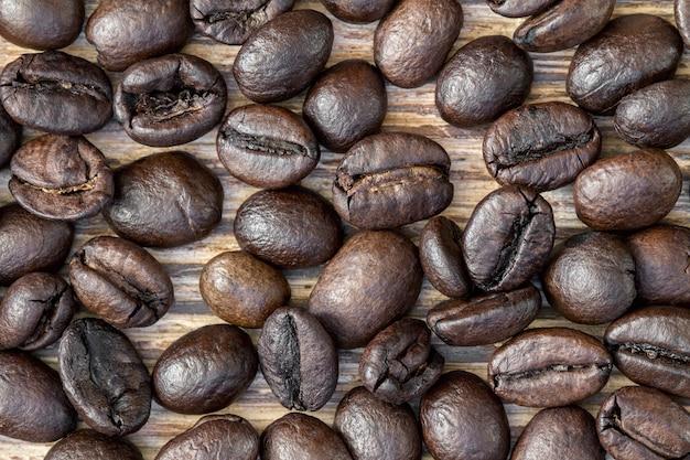 暗い背景の木のコーヒー豆のクローズアップ。上面図