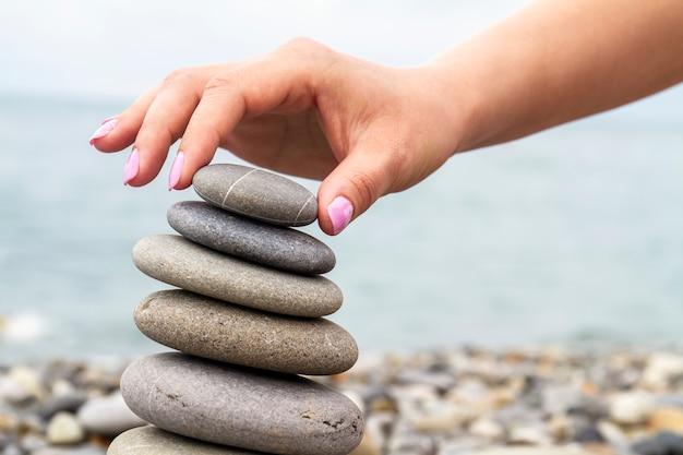女の子は小石のビーチで海岸に海の石のピラミッドを構築します。調和とバランスの概念。