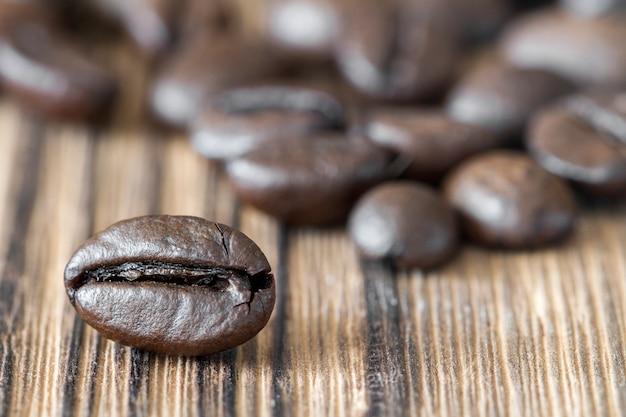 暗い背景の木のコーヒー豆のクローズアップ。