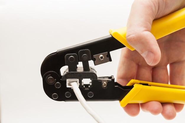 白い背景の上の手で圧着工具。黄色の圧着ペンチのクローズアップ。