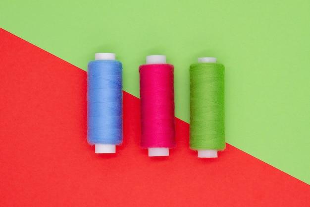 Вид сверху разноцветных швейных барабанов на цветном фоне