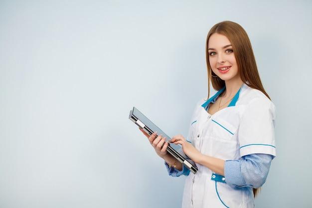 白い背景に分離されたタブレットコンピューターを使用して幸せな女医。白いコートで美しい少女