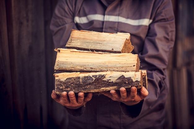 家を暖めるために用意された積み上げ薪の山。男は薪を手に持っています。