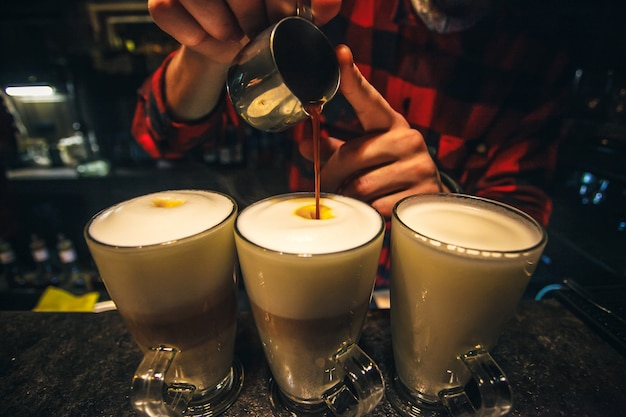 コーヒー作りバリスタはシナモンをラテまたはカプチーノの新鮮なカップに注ぎます。