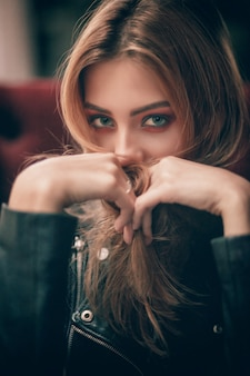 Портрет красивой девушки в черной кожаной куртке