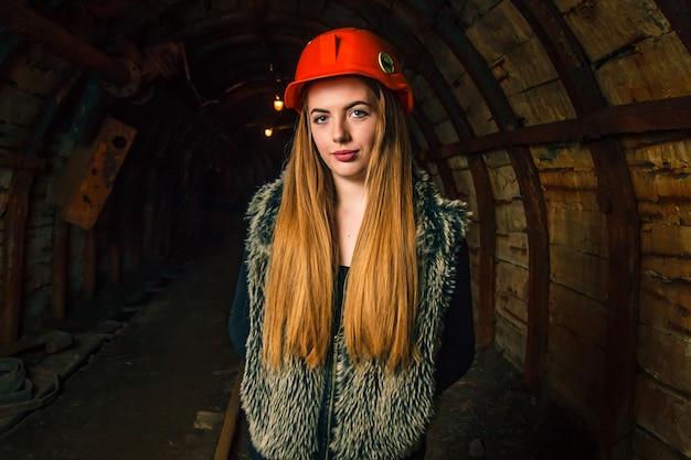 炭鉱でオレンジ色のヘルメットで美しい少女。スペースをコピーします。