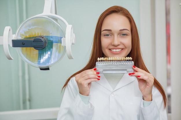 歯医者で美しい笑顔を持つ少女のクローズアップ。歯科歯科医はオフィスで歯の色を一致させます。