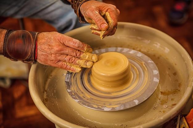主人は陶芸家の輪の上に粘土のコップを作る。