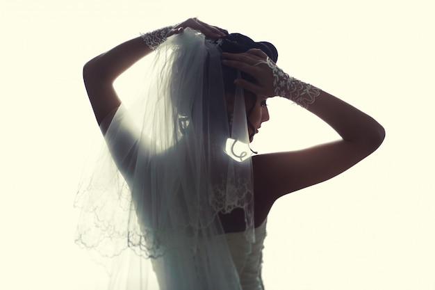 窓の近くに立っている美しい花嫁。白いウェディングドレスの少女。