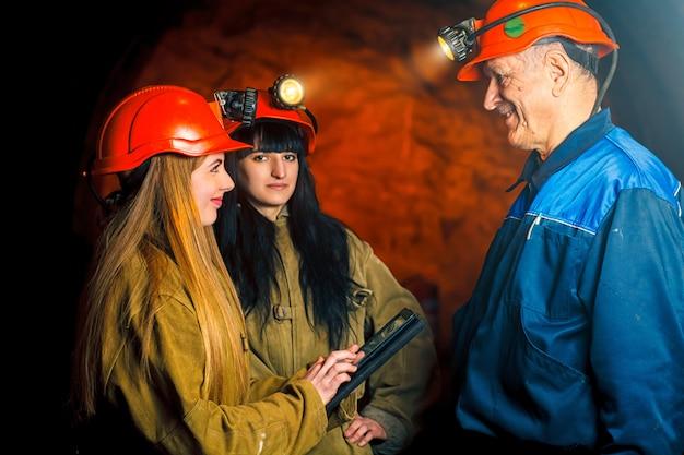 赤いヘルメットと彼女の手に電子タブレットを持つ美しい少女