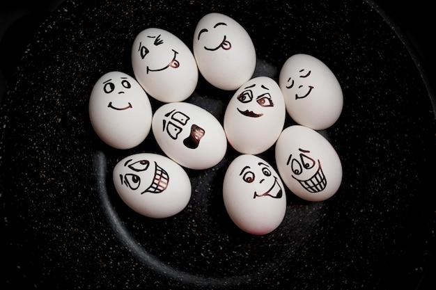 Эмоциональные яйца на сковороде. настоящие яйца с ручной росписью. копировать пространство