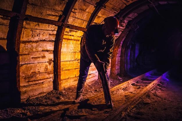 鉱山労働者が炭鉱で削岩機を働いています。炭鉱で働く。鉱山労働者の肖像画。スペースをコピーします。