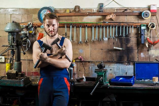 Механик в гараже стоит у рабочего стола с молотками в руках.