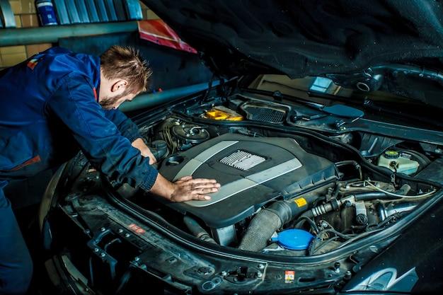 車のモーターで働くメカニック。自動車修理、サービスセンター。
