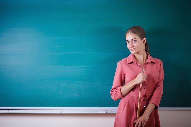 若い女性教師は、ポインターで黒板に立っています。