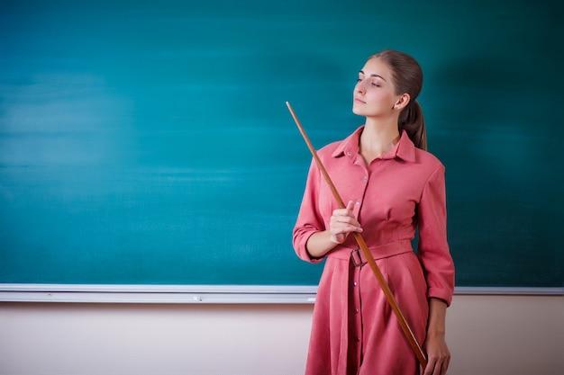 若い女性教師は、ポインターで黒板に立っています。学校の時刻表およびその他の情報のテンプレート。コピースペース。