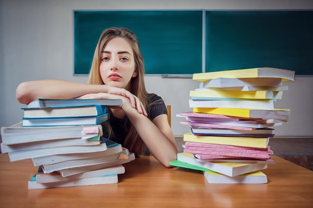 Разочарованный студентка, сидя за столом с огромной кучей учебников в классе