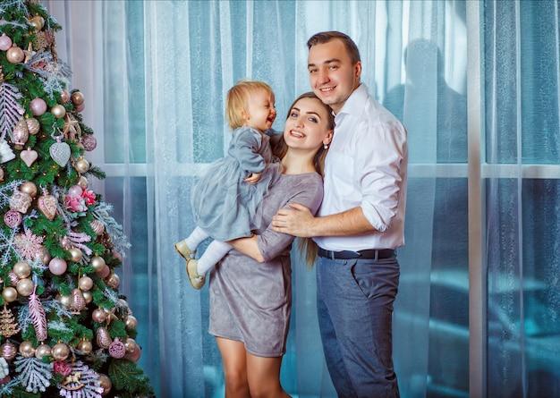 Родители и маленькая дочь ждут рождества, стоя возле новогодней елки
