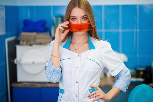 医療コンセプト。オレンジ色の安全メガネを保持している白いコートで美しい少女。