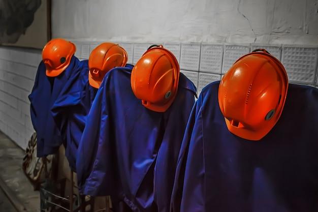 鉱夫のオーバーオールとオレンジ色のヘルメット。鉱夫の服