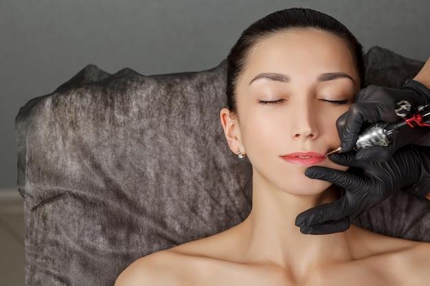 Молодая красивая женщина, делая перманентный макияж в косметологическом салоне