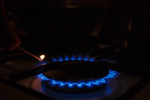 燃焼プロパンガスを使用したキッチンガスコンロ。マッチでガスストーブを照らす男。