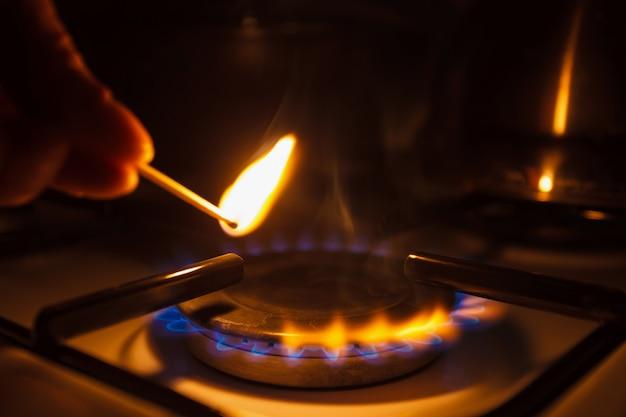 Кухонная газовая плита с горящим огнем пропан газ. мужчина зажигает газовую плиту спичкой.