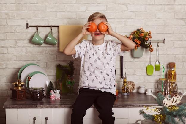 美しい小さな金髪の少年は台所のテーブルに座って、オレンジで目を閉じます。面白い写真