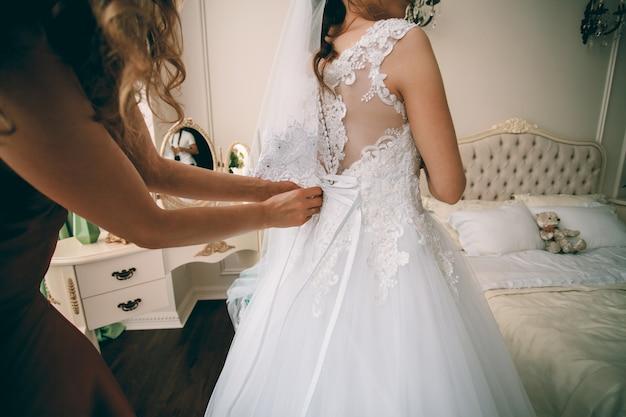 Шикарная невеста в белом роскошном платье готовится к свадьбе. женщина надевает платье