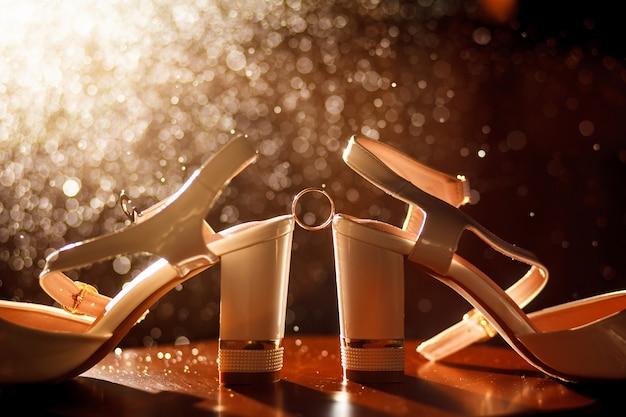 花嫁の靴の間の結婚指輪。花嫁の輝く靴の間に結婚式の黄金の指輪。