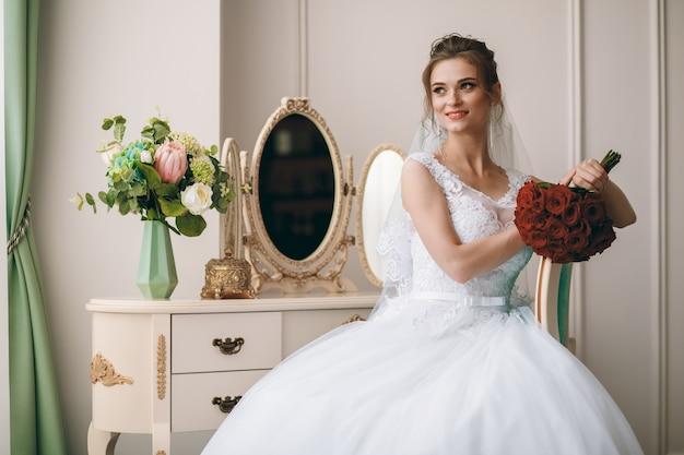 巻き毛のヘアスタイルと寝室の窓の近くに座って長いベールを持つ白い絹のドレッシングガウンの美しい花嫁の肖像画スペース。