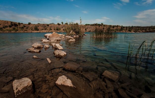 岩と山で泳ぐための美しい透明な水の泉。