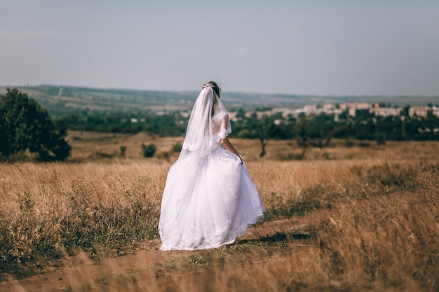 ロマンチックな美しい花嫁。ウェディングドレスを着た女性がフィールドを走る