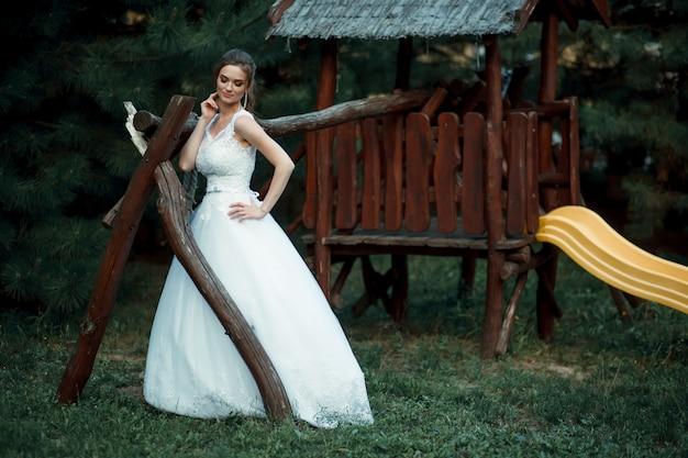 緑豊かな庭園に立っている白いウェディングドレスの美しいアジアの女性の花嫁