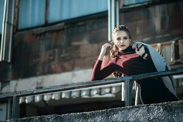 黒のジーンズと濃い赤のバッグを持つ若いファッショナブルな美しい女性