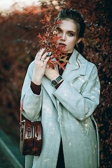 灰色の長いコート、黒のジーンズと濃い赤のバッグの若いおしゃれな美しい女性。プロのモデル。