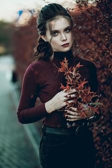 黒のジーンズと濃い赤のバッグを持つ若いおしゃれな美しい女性。プロのモデル。